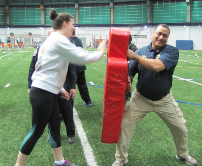Man holding red defense pad, while woman is punching the pad.