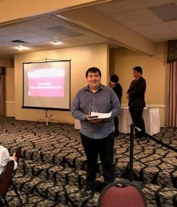 Jason Smyth holding Spotlight of the Year Award from the Office of Residence Life in the Drumlins Ballroom