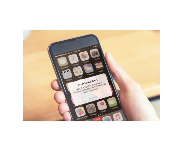 Hand holding cell phone with emergency alert message