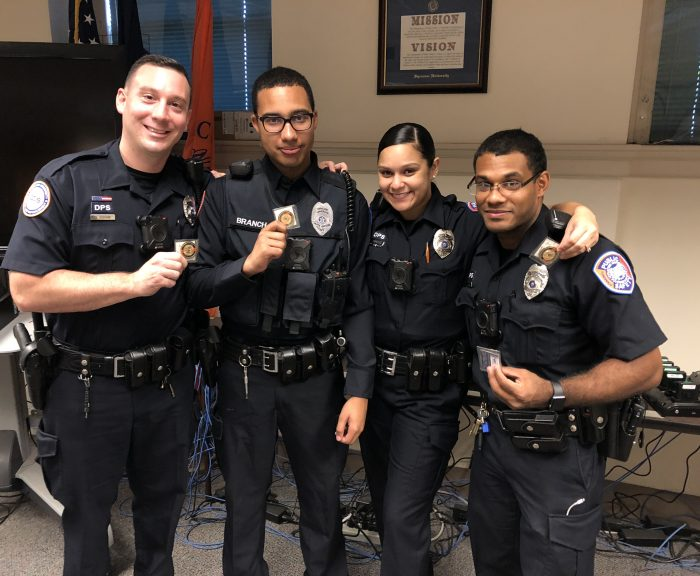 Officers (left to right) Dishaw, Branch, Ramirez & Alvarez standing together holding up their challenge coins