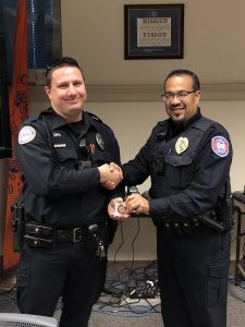 Officer Lebron presenting Officer Pearson with challenge coin while shaking hands.