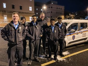 Group of six DPS community service officers posing with DPS shuttle van